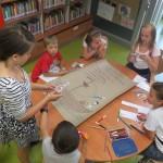 Dzieci siedzą wokół stołu, na nim duży arkusz papieru z narysowanym statkiem