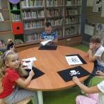 Dzieci siedzą wokół stołu i przygotowują pirackie bandery