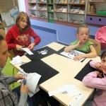 Dzieci siedzą przy stole i przygotowują pirackie bandery