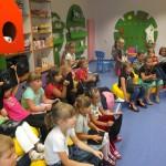 Dzieci siedzą i słuchają prowadzącej, jednocześnie trzymają wykonane przez siebie pirackie bandery