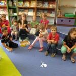 Dzieci siedzą na stopniach i słuchają