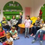 Dzieci siedzą, słuchają i wykonują gesty rękoma