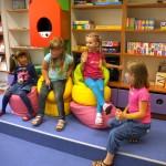 Cztery dziewczynki siedzą na pufach
