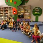 Dzieci siedzą w rzędzie i słuchają