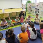 Dzieci siedzą w kółku na podłodze, jedna dziewczynka siedzi w środku, wszyscy słuchają instrukcji bibliotekarki