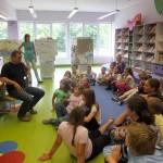 Dzieci siedzą na podłodze i słuchają wypowiedzi gościa