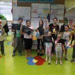 Dzieci prezentują swoje bandery na tle ścianki wystawowej
