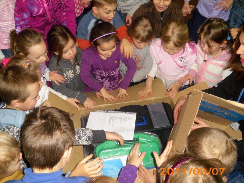 Dzieci otwierają paczki z przyborami badawczymi