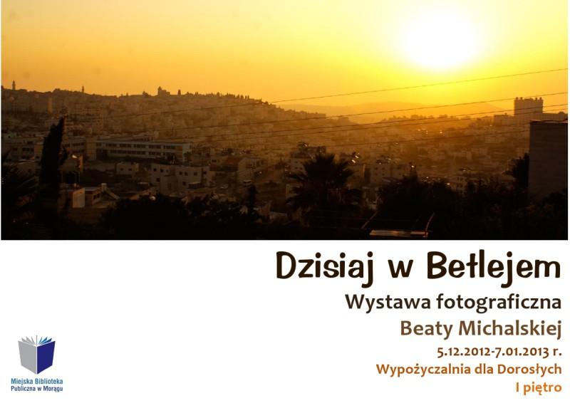 """Plakat wystawy """"Dzisiaj w Betlejem"""", na plakacie panorama miasta podczas zachodu słońca"""