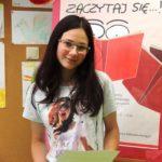 Uczestniczka konkursu z dyplomem i książką