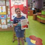 Młoda uczestniczka z książką i dyplomem