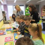 Dzieci przeglądające książki o Kici Koci