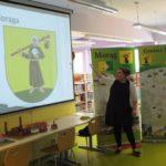Osoba prowadząca spotkanie pokazuje na tablicy godło Morąga. Za nią stoją banery przedstawiające mapę Morąga oraz gminy Morąg.