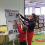 Dziecko wspólnie z bibliotekarką przyczepiają zdjęcie do flipcharta.