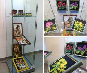 Prace autorki w gablocie, przedstawiają: kwiaty, tygrysa, Jezusa