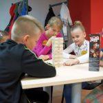 Kilkoro dzieci siedzi przy stole i gra w Jengę.