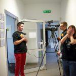 Operator kamery nagrywa materiał z mężczyzną. Kobieta stojąca obok kamerzysty zakrywa twarz dłońmi.