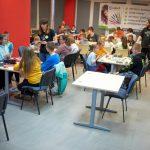 Uczestnicy siedzą przy stolikach i grają w gry.