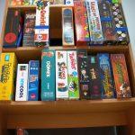 Regał z półkami, na których poukładane są gry.