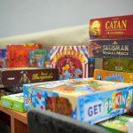 Kilkanaście gier planszowych w pudełkach poukładanych na stole.