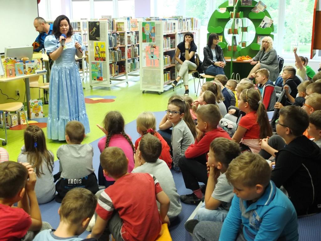 Spotkanie autorskie w oddziale dla dzieci. Autorka rozmawia z dziećmi siedzącymi przed nią. W tle widać regały z książkami i ustawione na stoliku książki.