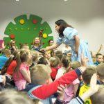 Zdjęcie grupowe. Dzieci podniesionymi rękami zgłaszają się do odpowiedzi. Prowadząca pochyla się z mikrofonem w stronę jednego z dzieci.