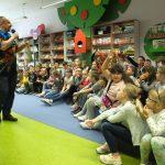 Prowadzący spotkanie stoi przed dziećmi z mikrofonem i książką. Dzieci mają ręce podniesione w geście zgłaszania się. W tle widać dekoracyjne regały i półki z książkami.