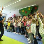 Mężczyzna prowadzi zabawę ruchową. Dzieci naśladują jego ruchy.