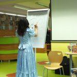 Prowadząca stoi przy tablicy i tworzy rysunek markerem. Obok stoi krzesło.