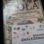 """Owinięta folią książka """"Zioła. Nowa encyklopedia"""". Na okładce widnieje kartka z napisem """"Brawo! Znaleziona!"""""""