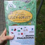 """Ręka trzymająca książkę """"Pamiętnik Zuzy-Łobuzy"""". Na okładce owiniętej folią książki znajduje się kartka z napisem """"Brawo! Znaleziona!"""""""