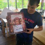 """Nastoletni chłopiec w granatowej koszulce trzyma w rękach owiniętą w folię książkę o kobietach. Na okładce książki kartka z napisem """"Brawo! Znaleziona!"""""""