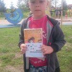 """Chłopiec w czapce z daszkiem trzyma w ręku zafoliowaną książkę z kartką """"Brawo! Znaleziona"""""""