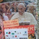 """Ręka trzymająca książkę """"Przy stole z papieżem Franciszkiem"""" . Na okładce książki kartka """"Brawo! Znaleziona!"""". Książka jest owinięta folią."""