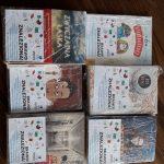 """Książki z kartkami """"Brawo! Znaleziona!"""" ułożone na brązowym blacie. Książki są zawinięte w folię."""