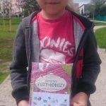 """Chłopiec trzymający w ręku książkę """"Pamiętnik Zuzy-Łobuzy"""""""