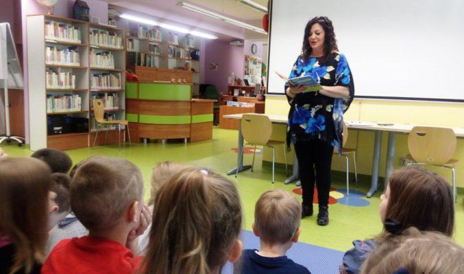 Kobieta z książką w ręku stoi przed grupą przedszkolaków
