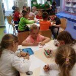 Dzieci siedzą przy stolikach i rysują obrazki