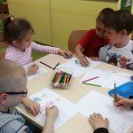 Dzieci przy stoliku tworzą prace plastyczne