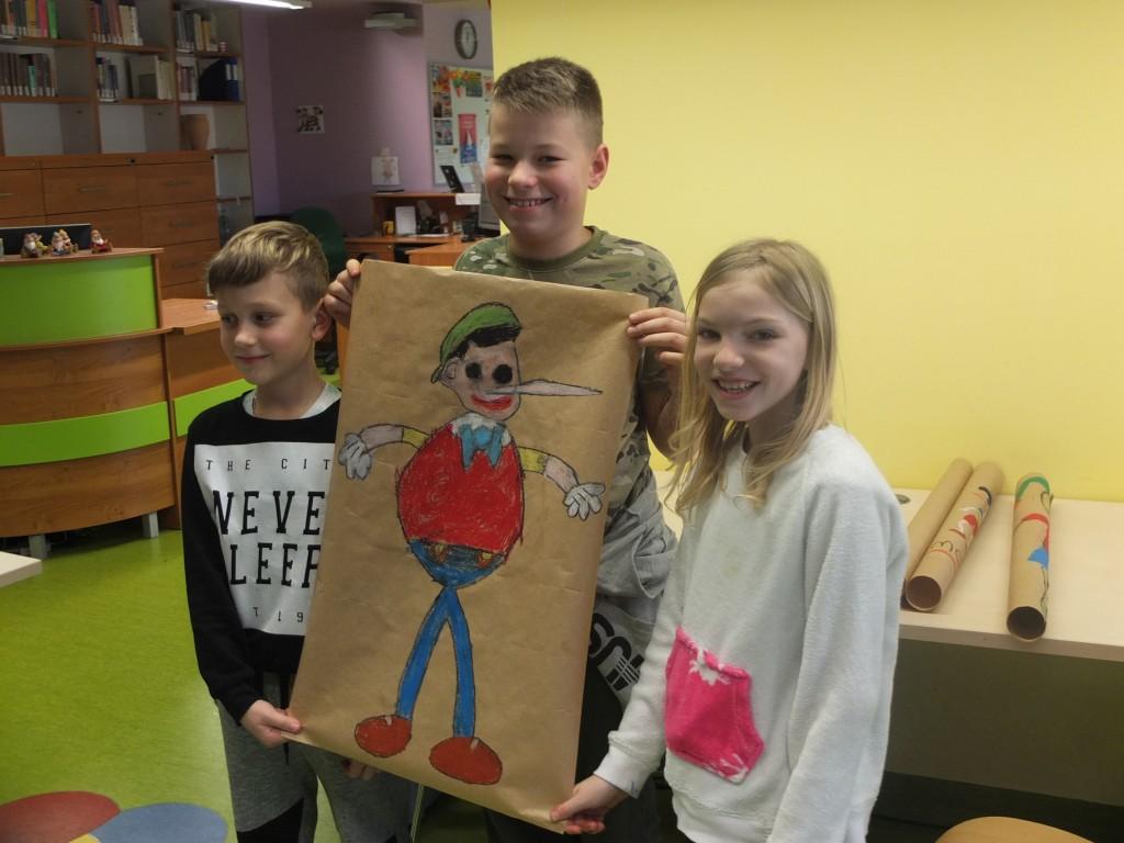 Dzieci pokazują rysunek Pinokia