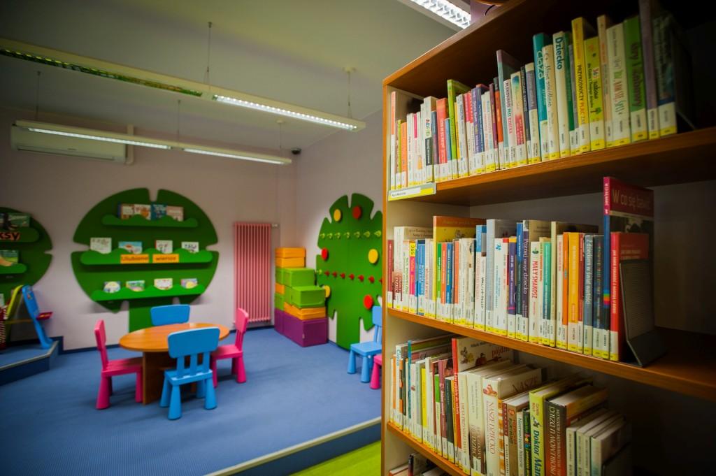 regał z książkami dla rodziców, w tle kącik dla małch dzieci z małym stolikiem i krzesełkami