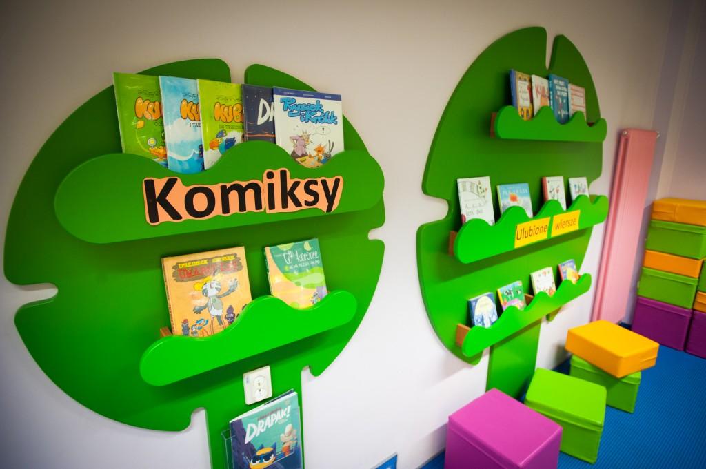 zielone drzewka na ścianie z pułeczkami na książki