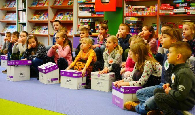 Dzieci siedzą na podłodze i słuchają wychowawcy, przed nimi stoją kartony z książkami