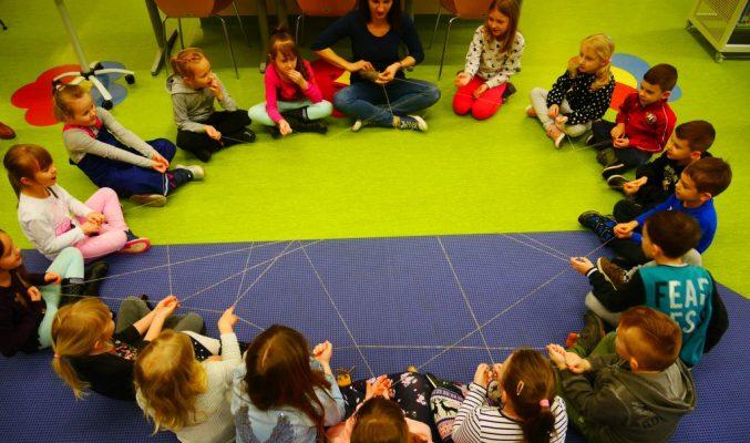 Dzieci siedzą w kółeczku na podłodze i wykonują polecenia prowadzącej