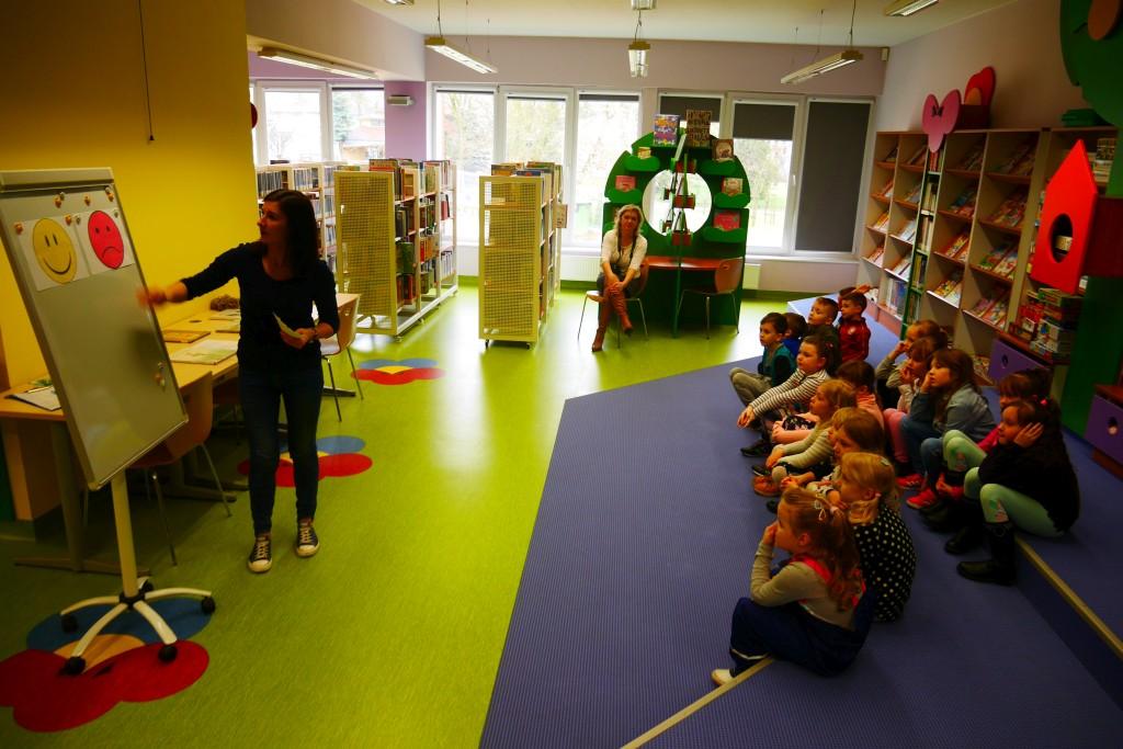 Prowadząca wyjaśnia dzieciom zadanie do wykonania na tablicy magnetycznej