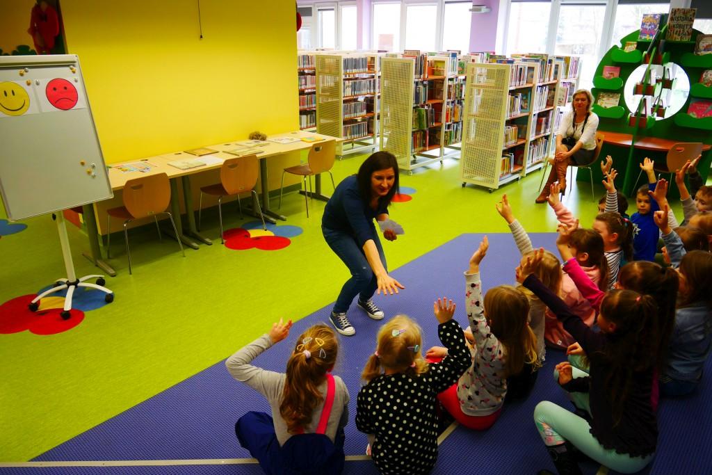 Dzieci siedzą na podłodze i zgłaszają się do wykonania zadania przygotowanego przez prowadzącą zajęcia