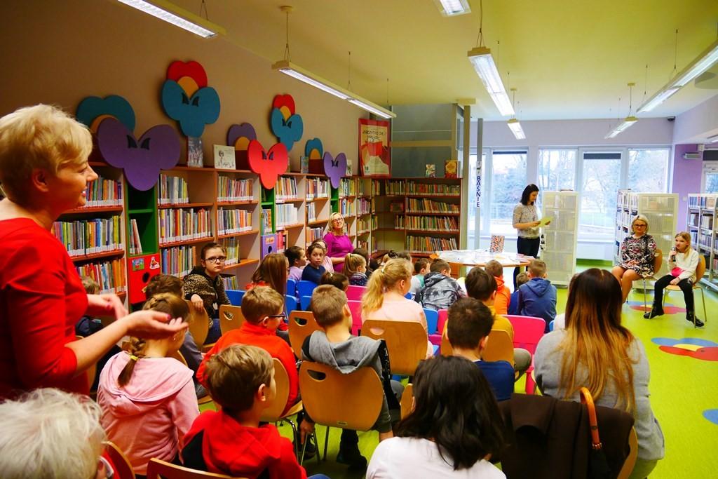 Dzieci siedzą na krzesełkach i słuchają wypowiedzi autorki wystawy