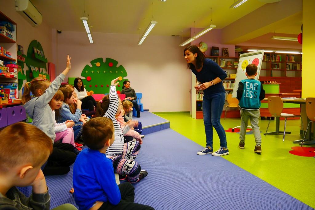 Dzieci siedzą i zgłaszają się do wykonania zadania na tablicy magnetycznej