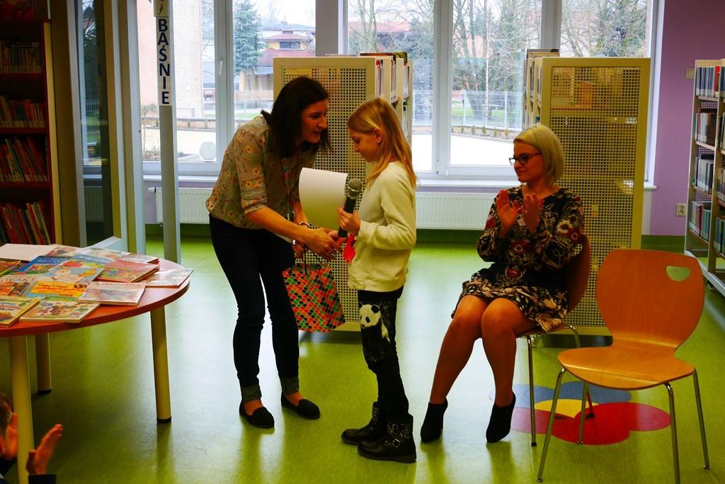 Bibliotekarka wręcza dyplom autorce wystawy