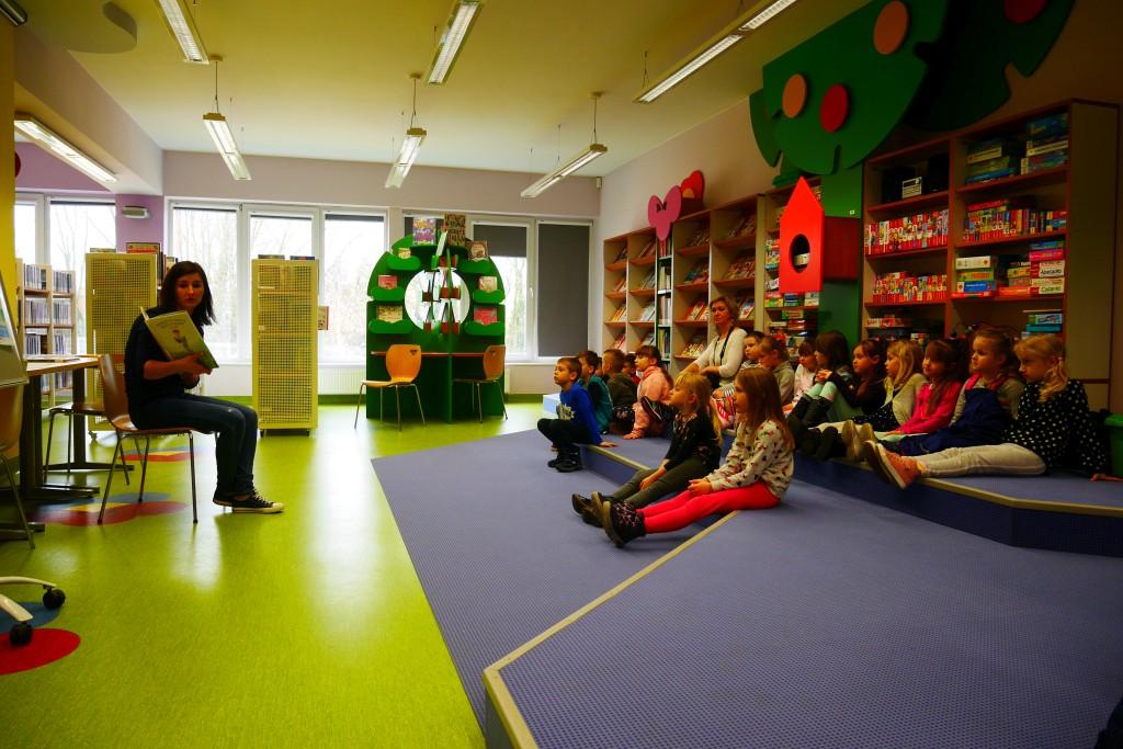 Dzieci siedzą na podłodze, przed nimi prowadząca prezentuje książkę